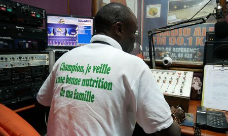 A radio DJ wearing a shirt with SPRING's messaging produces a radio program on water, sanitation, and hygiene at Al Fayda FM in Kaolack.