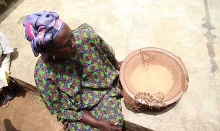 A woman demonstrates how she covers cereal with a transparent cloth to keep flies away.