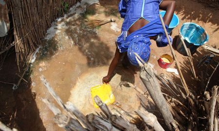A community member cleans a house-hold latrine and recovers it to prevent flies.