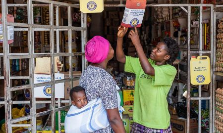 """Jessica Namusoke, listens to Winnie Nanyonga, a shopkeeper, as she explains about fortification. To inform the public about how to identify fortified products, SPRING organized a media campaign with radio talk shows. Additionally, 10,000 posters and 40,000 cutouts resembling fortified products on the market were distributed to shops and supermarkets. Each encouraged consumers to look out for the big blue """"F"""" on the packs of products to know if they are fortified or not."""