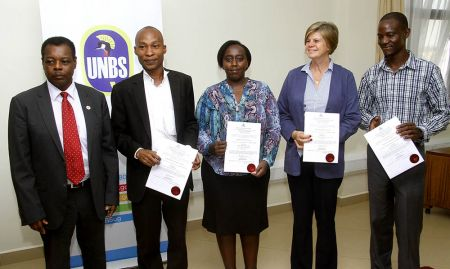 During a laboratory recognition ceremony, representatives of accredited laboratories pose with their certificates of recognition with Ben Manyindo (far left), the executive director of UNBS. With support of SPRING/Uganda, UNBS trained, assessed, and recognized five laboratories to help with the analysis of fortified foods.