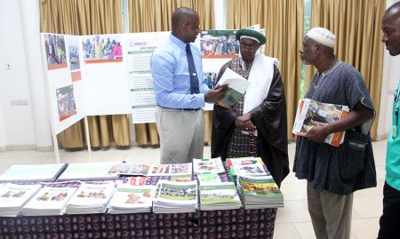Babajide Adebisi (left, SPRING Deputy Chief of Party-Programs) hosts a team from Ghana Health Service Northern Regional Directorate at the nutrition table. Listening attentively are Dr. Jacob Mahama (Regional Health Director and Chairman of the event) and Alhaji Sofo Mutaru (retired Regional Nutrition Officer).