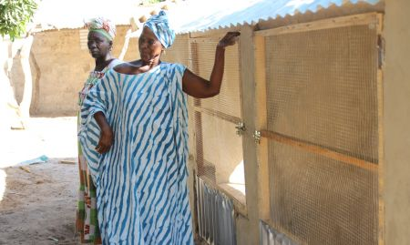 A leader of the local women's group stands proudly next to newly constructed chicken coop.