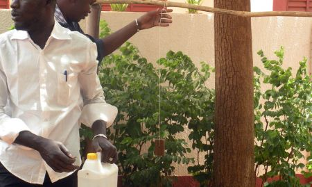 Placing the soap. SPRING/Mali stressed the use of soap, rather than using ash or just water, while handwashing. (Mopti, April 2015)