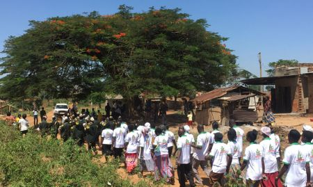 A band leads Village Health Team members on a march through Nsinze to gather attendees and promote the launch