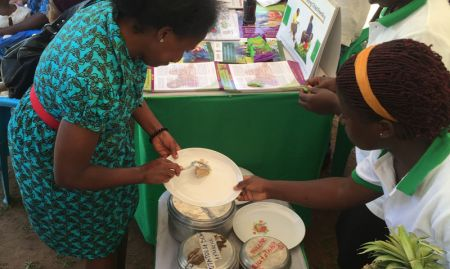 Guest of Honor Dr. Jacent Asiimwe prepares food to combine with micronutrient powders