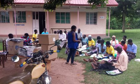 Rose Nakiwala, SPRING nutrition specialist, trains VHTs on the adherence calendar during a distribution event.