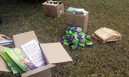 There are many materials to help with MNP distribution: adherence calendars (foreground), a pile of 60-day packaged supplies of MNPs (middle), boxes holding MNP stickers and reminder cards (behind MNP pile). All of these materials, in addition to the M&E tools, are brought to the VHTs and health workers during distributions. After VHTs return to their villages, they distribute these materials to households, while health workers distribute these materials straight from the health facilities.