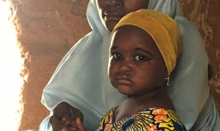 A young mother and her child participate in a C-IYCF support group in Kasuwan Magani ward, Kajuru LGA. She listens as the Community Volunteer discusses the importance of and ways to continue breastfeeding even when a mother works.