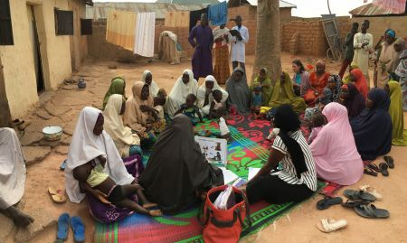 While men may not sit down to participate in C-IYCF support groups in Muslim communities like Kasuwan Magani ward, Kajuru LGA, men and children often congregate nearby to observe. Here Mr. Auwal Mohammed, the Chairman of the Kasuwan Magani Ward Development Committee, observes the support group. He too was trained in the C-IYCF Counseling Package and helped to train C-IYCF Community Volunteers. He has been an avid supporter of the program.