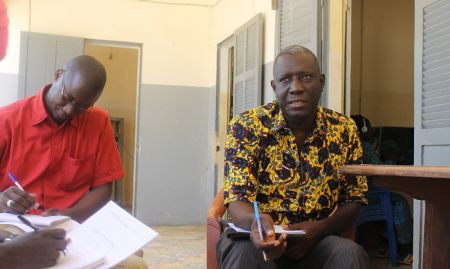 Ndef Leng Fatick's director, Pape Made Diouf, explains the community radio's mission while Ousmane Mbaye, SPRING's Mass Media Officer, takes notes.