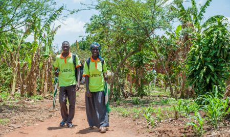 VHTs Rogers Wangemi and Salima Muyodi walk towards a homestead to distribute MNP to caretakers. There were two VHTs trained in each village of the community arm.