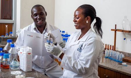 """Thomas Okoth and Justine Nabuuma of Uganda Industrial Research Institute (UIRI) perform an iron spot test on maize flour, to establish if the flour with the fortification logo is actually fortified. SPRING/Uganda worked with Uganda National Bureau of Standards (UNBS) to carry out random market surveillance to determine if products with the big, blue """"F"""" logo were actually fortified."""