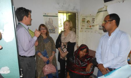SPRING Country Manager, Aaron Hawkins, and the USAID Mission Director and Assistant Administrator for Asia inside the Hochla Community Clinic discussing what SPRING does with its training for Government of Bangladesh staff.