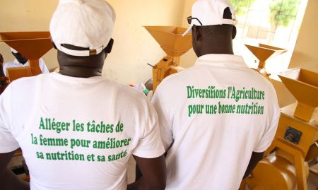 Trainees from the partner networks show off t-shirts bearing key messages about gender and nutrition. Left: Reduce women's workload to improve nutrition and health. Right: Diversify agriculture for good nutrition.