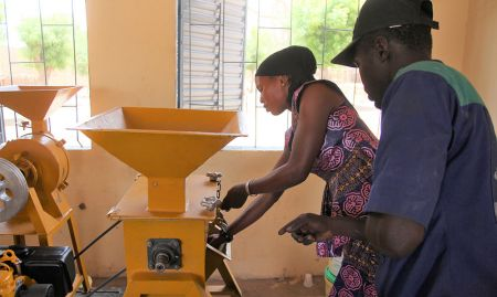 A technician from Hydro Bati Mec (HBM), the farming equipment company that supplied the processors, teaches a participant how to use it.