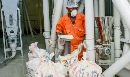 Paul Kato of Ntake Bakery and Company Limited, a wheat flour plant, adds fortificants to a dossier. SPRING/Uganda has been instrumental in ensuring that industries obliged to fortify do so. Five manuals and two training curricula have been produced to aid such processes and more.