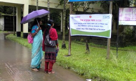 Two women admire a banner in Terokhada upazila