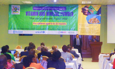 Dr. Alfred Boyo, the Nutrition and Child Health Specialist at USAID/Uganda, addresses the meeting. On the left is Mr. Manohar Shenoy, SPRING Chief of Party (Photo credit: Abel Muzoora).