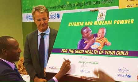 Dr. Boyo signs the commemorative micronutrient powder sachet (Photo credit Abel Muzoora).