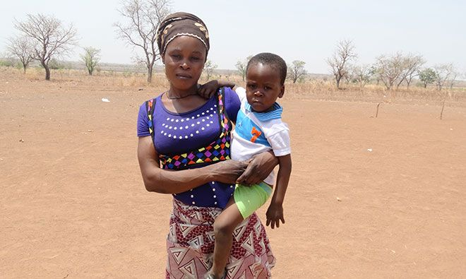 A woman holding her baby stands in a dusty field.