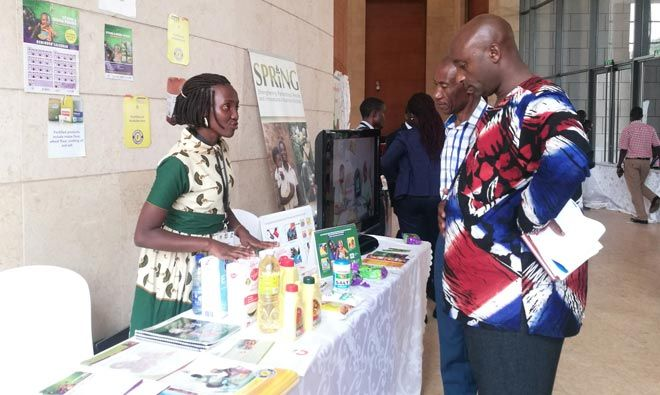 Jennifer Akello (R), a SPRING/Uganda staff, explains to Members of Parliament about SPRING/Uganda's work in the prevention and control of anemia and stunting through policy influence, food fortification and distribution of vitamin and mineral powders. This was during the inaugural Uganda Parliamentary Forum on Nutrition.
