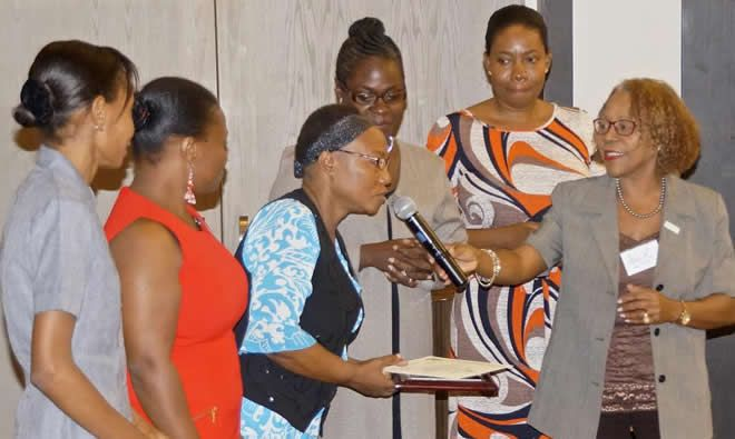Nicole Racine, SPRING/Haiti country manager handing the microphone to Center Nutrition Focal Point, Miss Ninette Dupuy with Trainers from Hopital Ste Therese de Hinche at the closing ceremony on October 13, 2015.