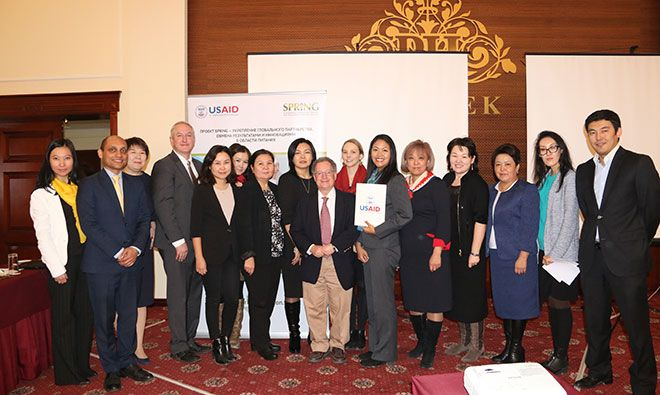 Roundtable participants stand in a line and smile at the camera