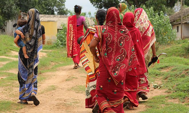 Several women walking down the road with their backs to the camera