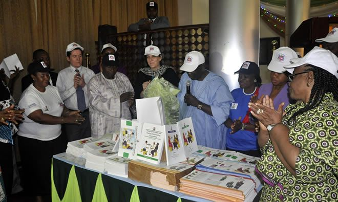 The Permanent Secretary of the Nigerian Federal Ministry of Health, his Excellency Ambassador Bala Sani (in blue), alongside the SPRING Nigeria team, looks over the package of resource materials on IYCF.