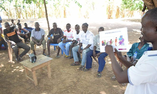 A group of fathers sits in chairs under a tree while one man uses a flip chart of good health behaviors to conduct a training.