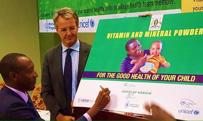 Dr. Boyo signs the commemorative micronutrient powder sachet (Photo credit Abel Muzoora )