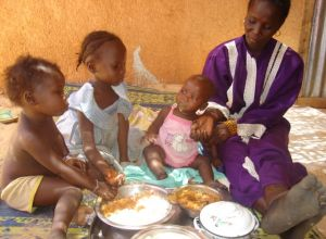 Woman feeding three seated children