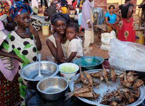 Fish sellers and an infant smile at a fish market in Guinea.