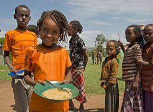 Young girl holding a bowl of food