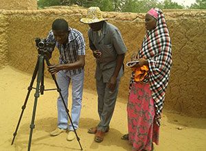 One man looking into a camera on a tripod while a man and woman watch