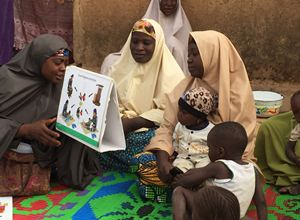 Young children accompanied their mothers while they listened to Mrs. Maryam Adams, a C-IYCF Community Volunteer in Kasuwan Magani ward in Kajuru LGA, discuss complementary feeding. C-IYCF Community Volunteers were observed to ask support group participants to explain the illustrations to ensure that they understood the messages.