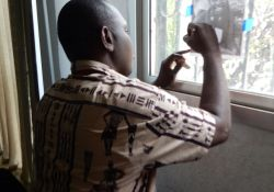 Ibrahima Lansana Kaba of the SMARTE Project of Winrock, International practices tracing in a window.