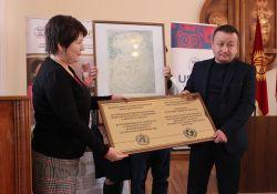 USAID Health Project Management Specialist Aisha Zhorobekova presents the BFHI certification plaque to Abdulbaki Yrysbekov, Director of Karakul General Medicine Practice Center in Jalalabad oblast.