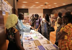 One of SPRING/Senegal's department coordinators, Yirime Faye, speaks to guests about SPRING's accomplishments in nutrition, hygiene and gender at one of the stands set up to showcase the project's achievements.