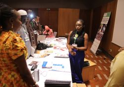 One of SPRING/Senegal's department coordinators, Fatou Kiné Camara, speaks to guests about SPRING's accomplishments in SBCC at one of the stands set up to showcase the projects achievements.