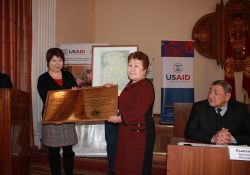 The Deputy Director of Ala-Buka FMC, Jumagul Tazhibaeva, accepts the BFHI certification plaque.