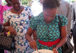 Guest of the Honor Dr. Jacent Assimwe demonstrates how to mix the MNPs into food