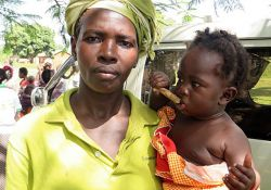 Rose Namukose, a beneficiary of the MNP program, shows off the baby who she has successfully enrolled