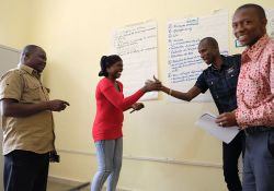 Staff participants conduct a role play, persuading each other to purchase their improved technology for making agriculture more nutrition sensitive.