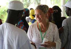 SPRING country program manager, Nathalie Albrow, chats with a guests at the Kaolack close-out event.