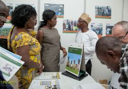 Ziba Dokurugu, SPRING/Ghana's Agriculture Advisor, explains SPRING's aflatoxin control programs to event participants visiting the SPRING booth.