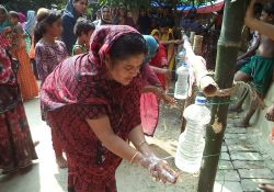 Woman washing her hands with a tippy tap
