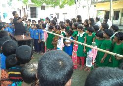 Group of children watching a man give a handwashing demonstration