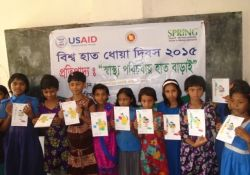 A class of children showing their drawings for Global Handwashing Day